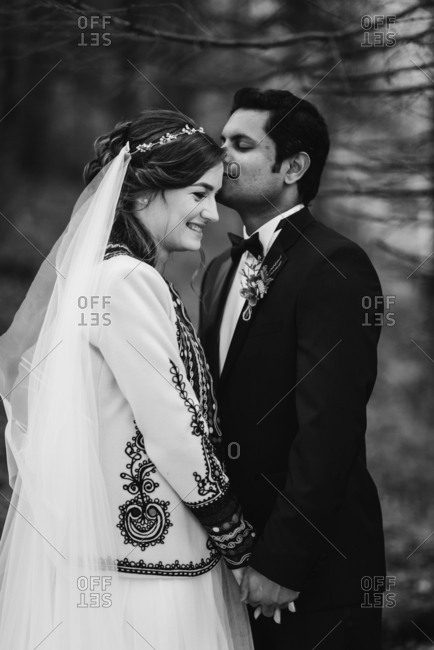 Groom kissing his bride's forehead in the forest in black and white