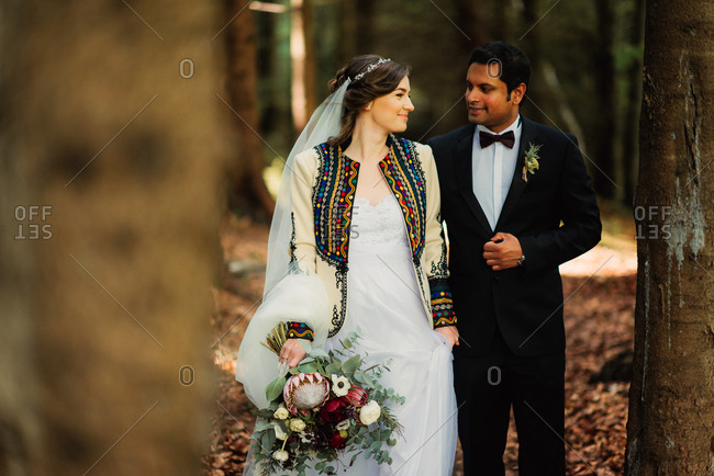 Bride and groom walking together in the forest