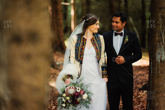 Newlywed couple walking together in the forest