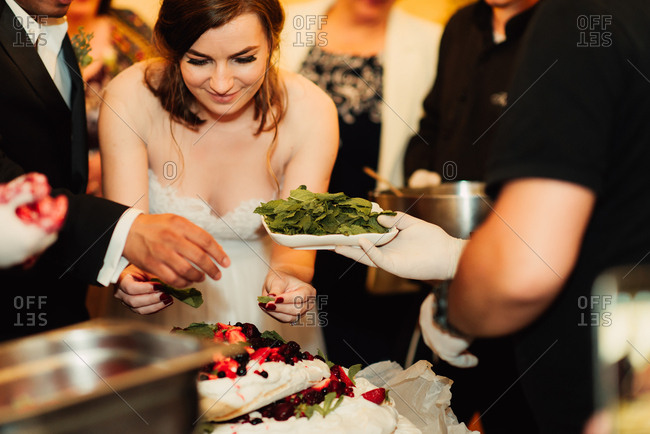 Couple decorating Pavlova with fruit and mint leaves