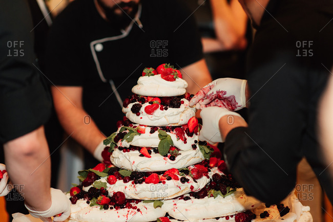 Bakers decorating Pavlova with fruit and mint leaves