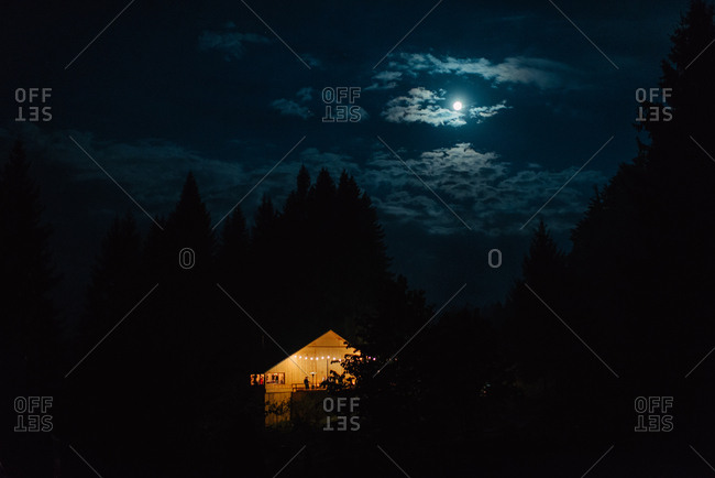 Rustic barn illuminated with lights under moonlight