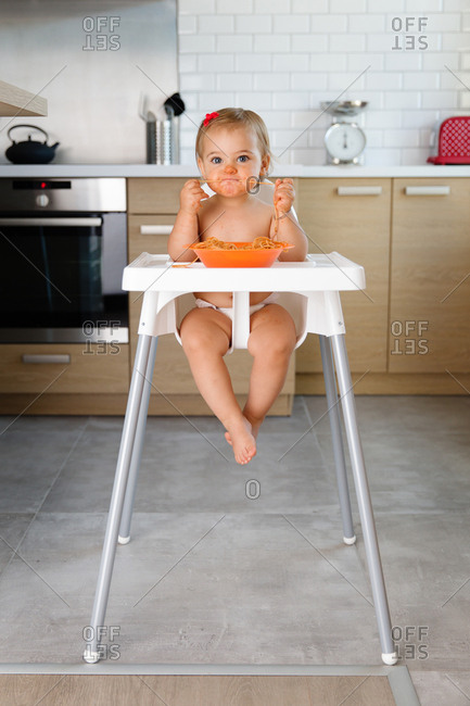 Toddler eating noodles in high chair