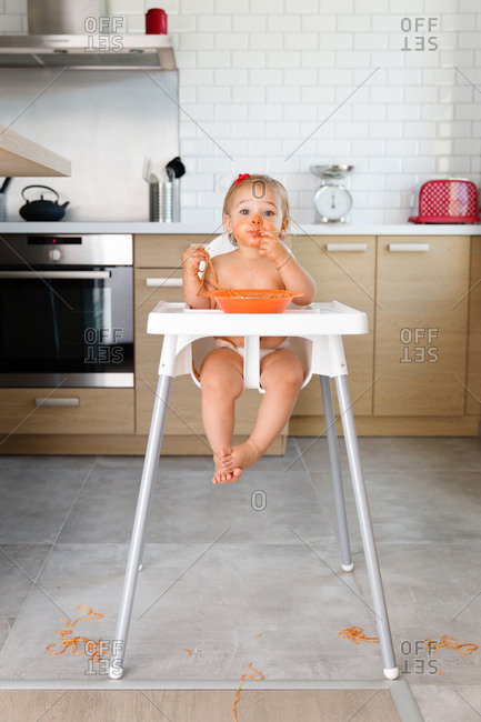 Toddler girl eating noodles in high chair