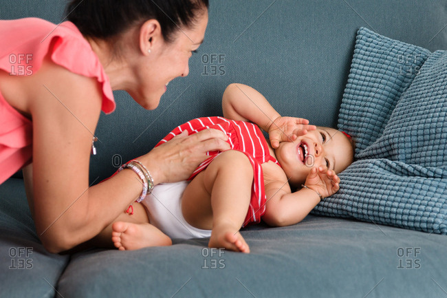 Mom tickling toddler girl on couch