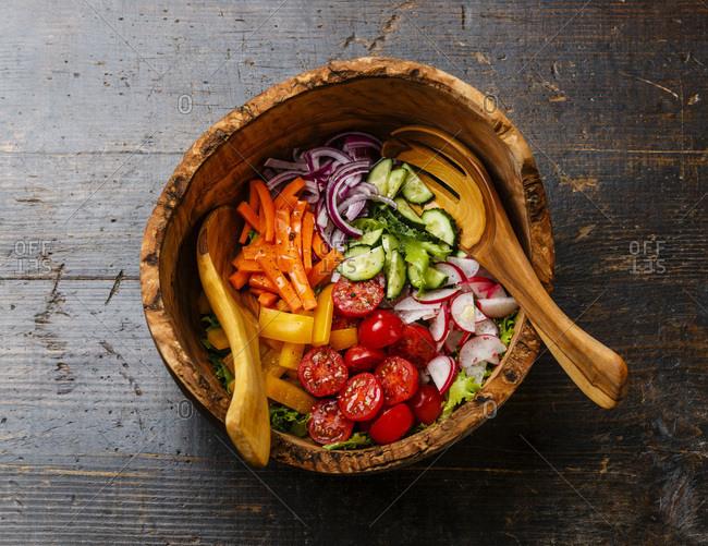 Fresh vegetable salad in olive wood bowl on wooden background