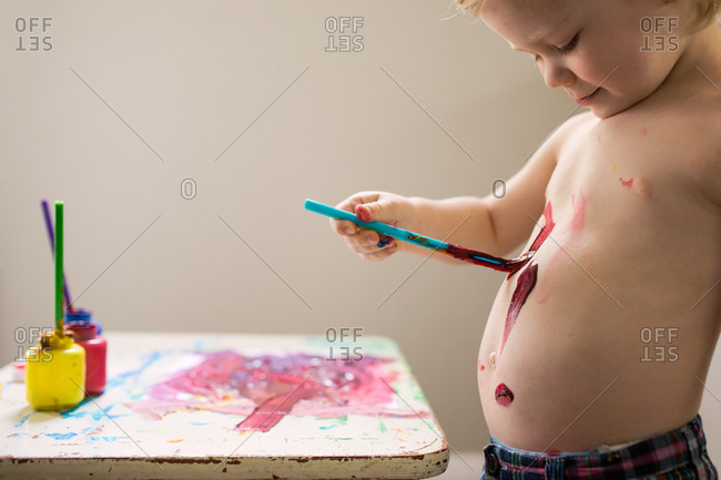 Little boy painting on his tummy