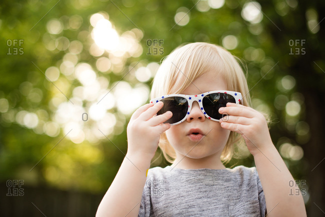 Portrait of a toddler boy trying on a pair of sunglasses