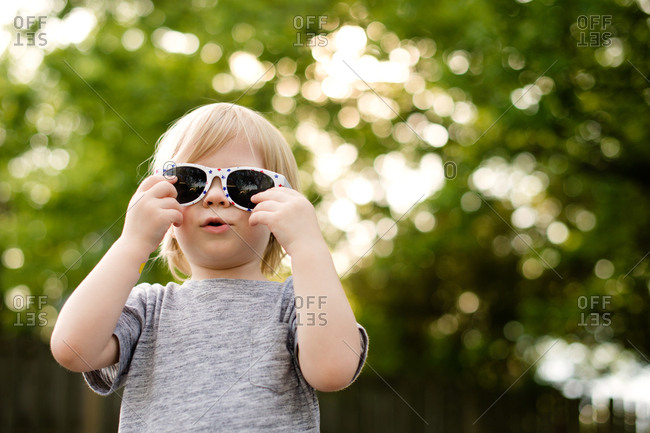 Toddler boy trying on sunglasses