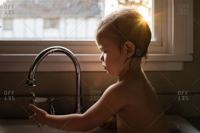 Toddler boy sitting in the kitchen sink putting his hand under the faucet