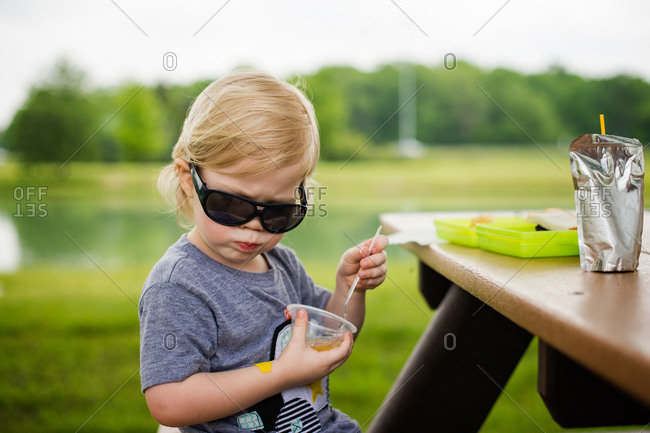 Toddler boy wearing sunglasses eating at picnic table