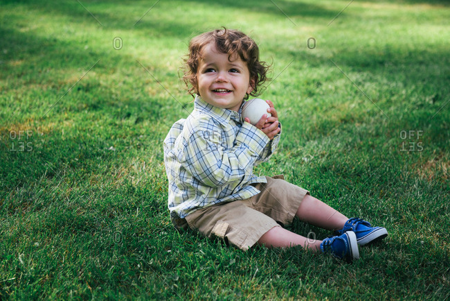 Toddler sitting in grass with ball