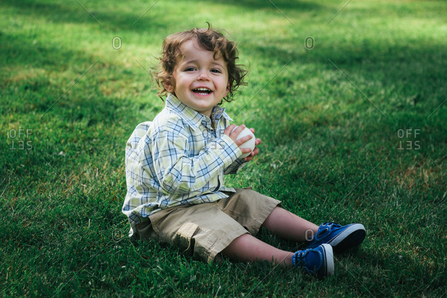 Toddler laughing in grass with ball