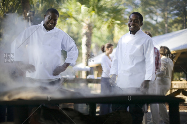 Two chefs cooking on an outdoor grill
