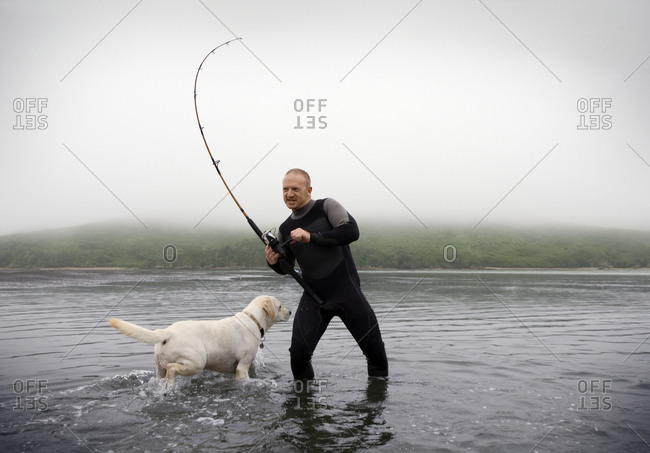 A man fly fishing with his dog