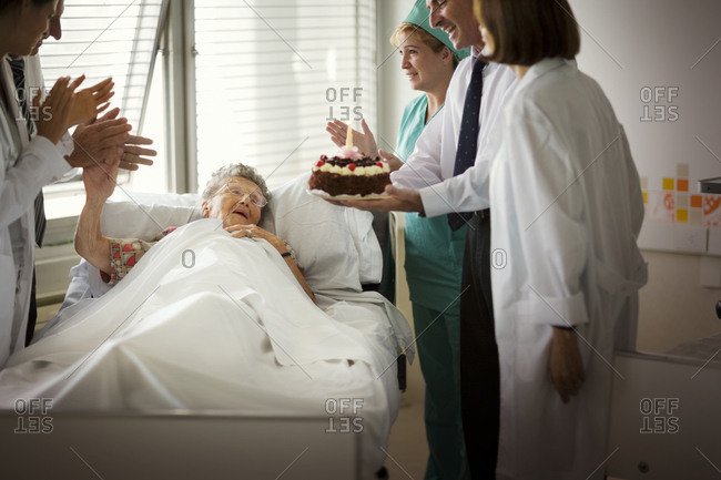 A group of doctors and nurses surprising an elderly patient with a birthday cake