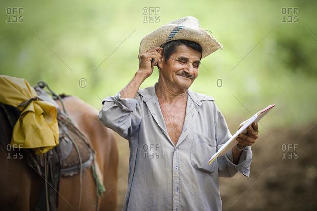 A man on a horse trek reading a map