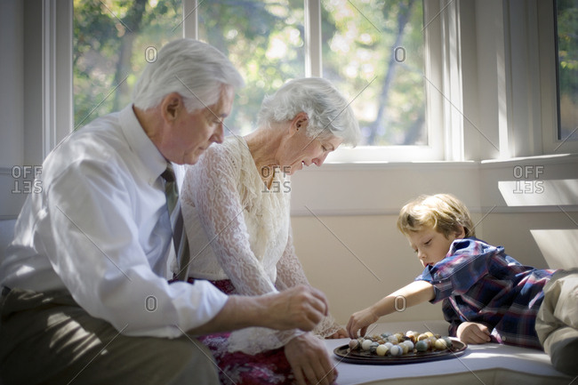 A young boy playing a marble game with his grandparents