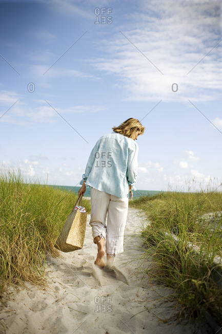 A woman walking on the sand to the beach