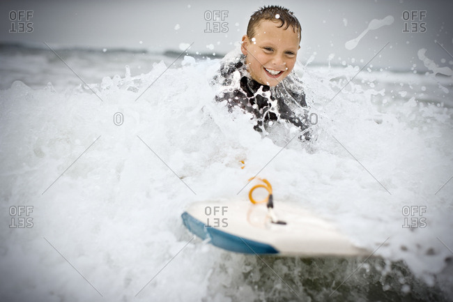 A young boy body boarding in the waves