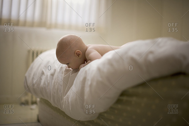 A baby looking down from the edge of a bed