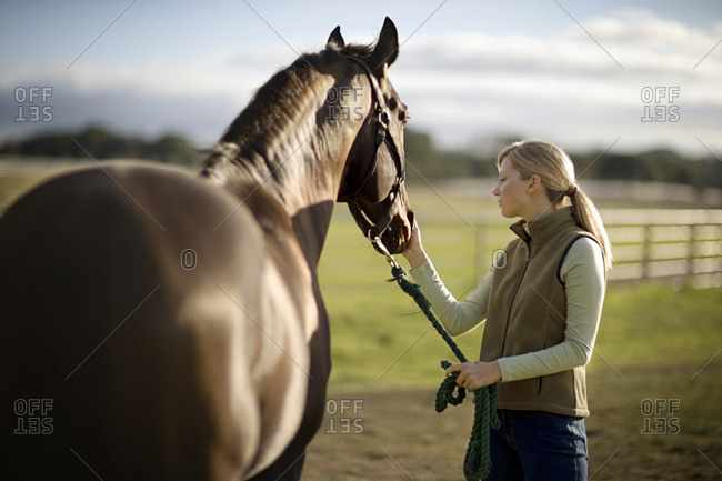 A young woman stroking her horse