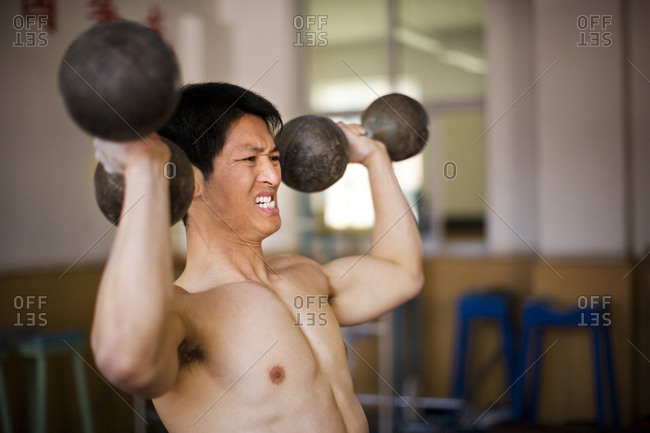 A young man lifting weights in a gym