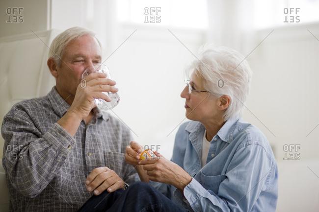 A senior woman helping her partner take his medication