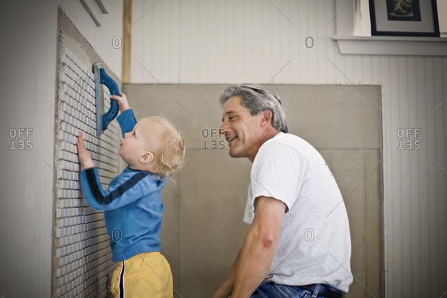 A toddler helping his grandfather with a DIY project