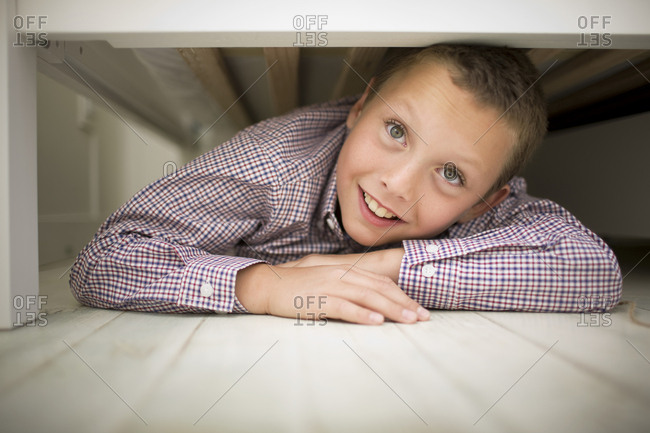 A young boy playing hide and seek under his bed