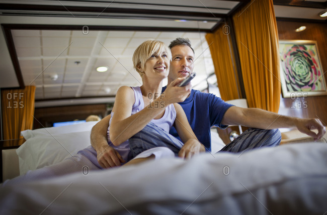 A couple relaxing on their bed watching TV