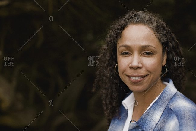 A smiling woman wearing hoop earrings