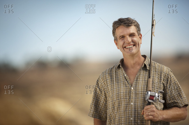 A smiling fisherman with his fishing rod