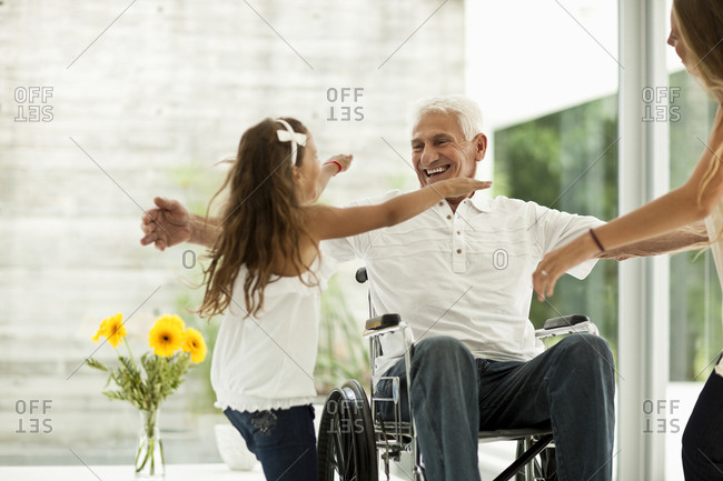 A senior man in a wheelchair being greeted by family