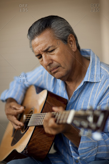 A man playing the acoustic guitar