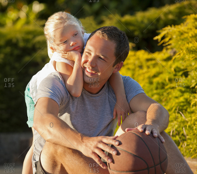 A father and daughter resting after playing basketball together