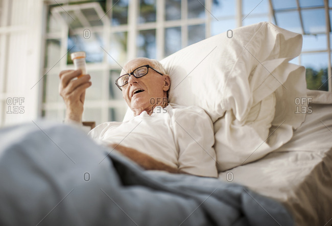 A senior man in a hospital bed reading his medication bottle