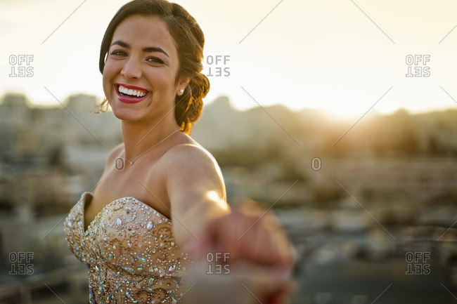A smiling young woman dancing in evening wear