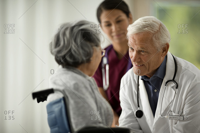 A doctor and nurse speaking with a senior patient