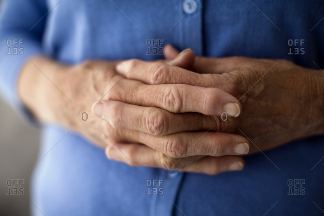 Clasped hands on a senior woman