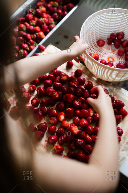 Girl with fresh strawberries in sink