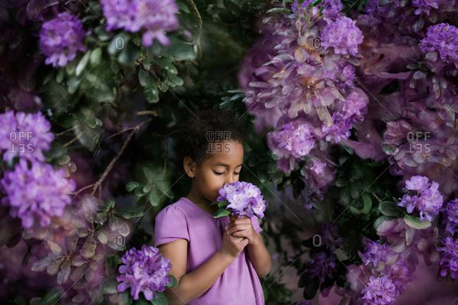 Girl smelling flowers in bush