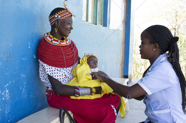 Nurse examining a baby on a mother's lap in Kenya, Africa