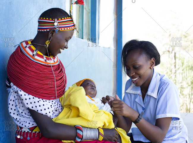 Nurse examining a little baby on a mother's lap in Kenya, Africa