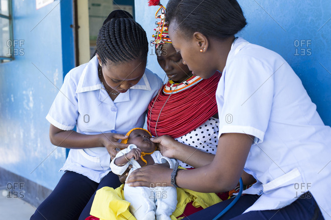 Nurses examining a baby on a mother's lap in Kenya, Africa