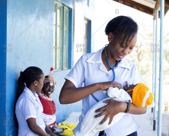 Nurse examining a baby with mother in the background in Kenya, Africa
