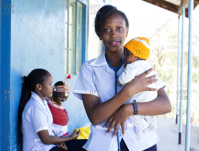 Nurse holding a baby with mother in the background in Kenya, Africa