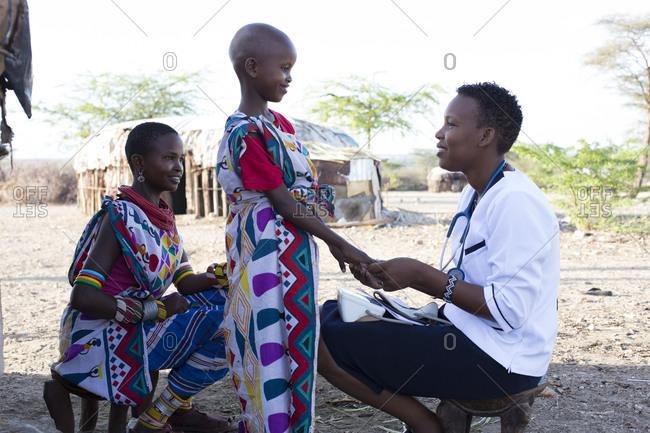 Kenya, Africa - April 25, 2017: Nurse examining Mother and daughter in Samburu village