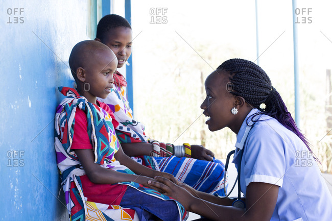 Nurse examining girl and her mother in clinic in Kenya, Africa