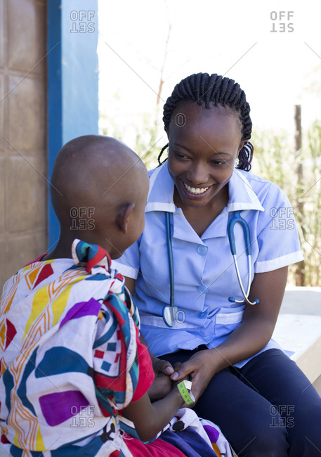Nurse examining a young girl in clinic in Kenya, Africa
